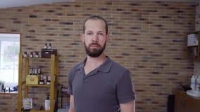 Um homem novo com uma barba na barbearia video estoque