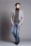 Um homem novo com uma barba, vestindo estar do revestimento e das calças de brim Imagem de Stock