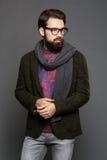 Um homem novo com uma barba, vestindo estar do revestimento e das calças de brim Imagem de Stock Royalty Free