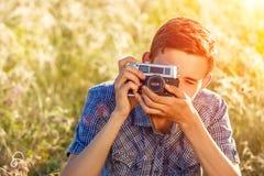 Um homem novo com uma câmera que toma imagens dos raios do sol do fundo natural matizados fotografia de stock