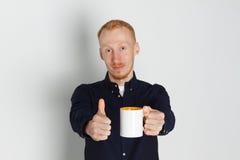 Um homem novo com uma caneca de chá ou de café Ele satisfeito Fundo branco Homem do ruivo com caneca branca Foto de Stock Royalty Free
