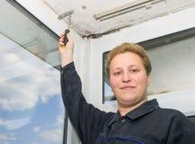 Um homem novo com uma chave de fenda aperta o parafuso fotografia de stock royalty free