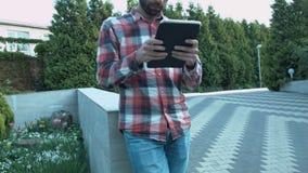 Um homem novo com uma tabuleta em suas mãos está inclinando-se no parapeito no parque video estoque
