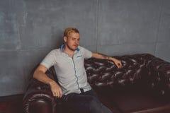 Um homem novo com uma tatuagem em sua mão que levanta em um sofá de couro roupa do estilo da rua: camisa branca e calças de brim  fotografia de stock