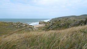 Um homem novo com uma trouxa em seus ombros anda ao longo da costa perto do mar filme