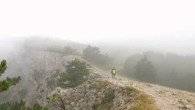 Um homem novo com uma trouxa em seus ombros anda ao longo de um cume da montanha rochosa coberto com as nuvens vídeos de arquivo