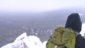 Um homem novo com uma trouxa em seus ombros aumenta à parte superior de uma montanha coberto de neve video estoque