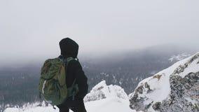 Um homem novo com uma trouxa em seus ombros, está sobre uma montanha coberto de neve e admira a paisagem filme