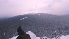 Um homem novo com uma trouxa em seus ombros, está sobre uma montanha coberto de neve e admira a paisagem video estoque
