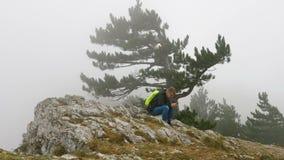 Um homem novo com uma trouxa em seus ombros senta-se em uma montanha rochosa coberta com as nuvens video estoque