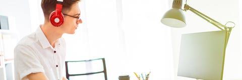 Um homem novo com vidros e fones de ouvido está trabalhando no computador Antes do indivíduo são uma placa magnética e os marcado imagem de stock royalty free