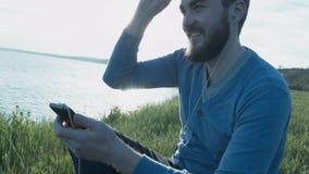 Um homem novo considerável nos vidros perto do mar no por do sol escreve sms em um smartphone Um homem à moda feliz com fones de  filme
