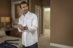 Um homem novo considerável obtém vestido no quarto fotografia de stock
