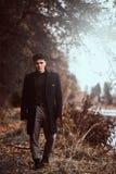 Um homem novo considerável que anda na floresta do outono foto de stock royalty free