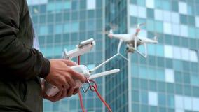 Um homem novo um homem controla um quadrocopter com um painel de controle moderno e um transmissor de RC Voo e película do homem  filme