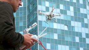Um homem novo um homem controla um quadrocopter com um painel de controle moderno e um transmissor de RC Voo e película do homem  video estoque