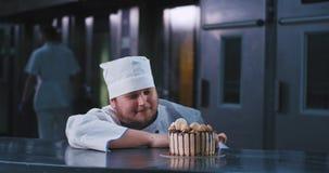Um homem novo de êxtase com uma barba curto espera pacientemente para escolher em seu bolo de aniversário bonito filme