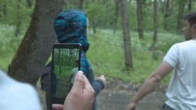 Um homem novo de caminhada em um t-shirt branco e em uma jovem mulher através de uma tela do smartphone Através do telefone um ho video estoque