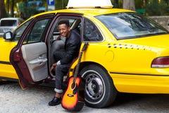 Um homem novo de sorriso no carro com a porta aberta do carro amarelo, olhando e sorrindo, com p? esquerdo fora, perto da guitarr foto de stock