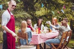 Um homem novo de sorriso shashliks vestindo de um churrasco do avental no f imagens de stock royalty free