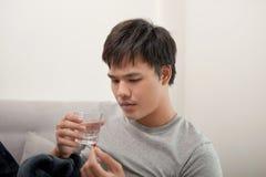 Um homem novo ? doente com gripe, encontra-se em casa sob uma cobertura, toma um comprimido foto de stock royalty free