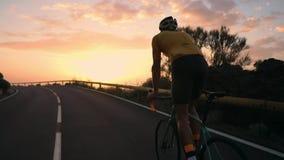 Um homem novo dos esportes que monta uma bicicleta em uma serpentina da montanha em uma opinião traseira amarela do capacete e do vídeos de arquivo