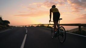 Um homem novo dos esportes que monta uma bicicleta em uma serpentina da montanha em uma opinião traseira amarela do capacete e do filme