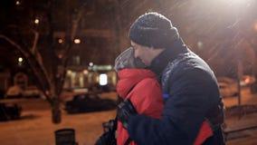 Um homem novo e uma mulher encontraram-se em uma noite do inverno no parque Relacionamento feliz dos pares video estoque