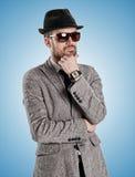 Um homem novo em óculos de sol de um chapéu do revestimento Fotografia de Stock Royalty Free