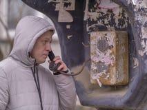 Um homem novo em um revestimento com uma capa está falando a um payphone velho na rua fotografia de stock royalty free