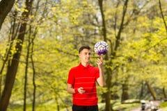 Um homem novo em um t-shirt vermelho joga com uma bola de futebol no parque verde Conceito do esporte fotografia de stock
