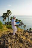 Um homem novo em um terno branco na praia imagens de stock royalty free