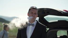 Um homem novo em um terno clássico, laço fuma VAPE Suportes ao lado do carro na natureza filme