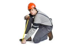 Um homem novo em trabalhar a roupa cinzenta e o capacete duro alaranjado que medem a área métrica na sala Imagem de Stock