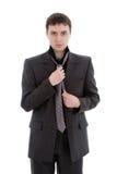 Um homem novo em um terno, amarra um laço. Imagem de Stock