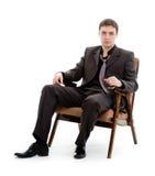 Um homem novo em um terno e em um laço, sentando-se em uma cadeira. Imagens de Stock Royalty Free