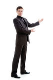 Um homem novo em um terno gesticula com suas mãos. Fotos de Stock