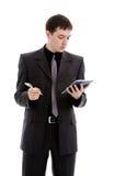 Um homem novo em um terno, olhares em um caderno. Foto de Stock Royalty Free