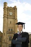 Um homem novo em um vestido da graduação. fotografia de stock
