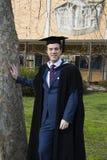 Um homem novo em um vestido da graduação. Foto de Stock
