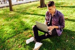 Um homem novo em uma camisa de manta, sentando-se em um gramado verde no parque, trabalhando em um laptop fotos de stock