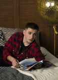 Um homem novo em uma camisa do moderno encontra-se em uma cama fotos de stock