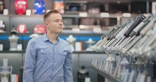 Um homem novo em uma camisa escolhe um misturador para sua cozinha em uma loja dos produtos eletrónicos de consumo video estoque