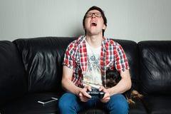 Um homem novo em uma camisa vermelha e na calças de ganga senta-se em casa e joga-se jogos de vídeo junto com seu cão O indivíduo imagem de stock