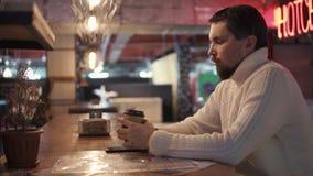 Um homem novo em uma camiseta morna bebe o café quente de um copo do cartão em uma barra video estoque