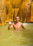 Um homem novo em uma mola mineral quente Imagem de Stock