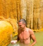 Um homem novo em uma mola mineral quente Turquia Karahayit perto do Imagens de Stock