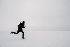 Um homem novo em uma trouxa preta e viagem na lagoa congelada imagens de stock royalty free