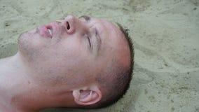 Um homem novo encontra-se na areia na praia fotografia de stock