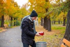 Um homem novo encontrou no parque um presente vermelho fotografia de stock royalty free